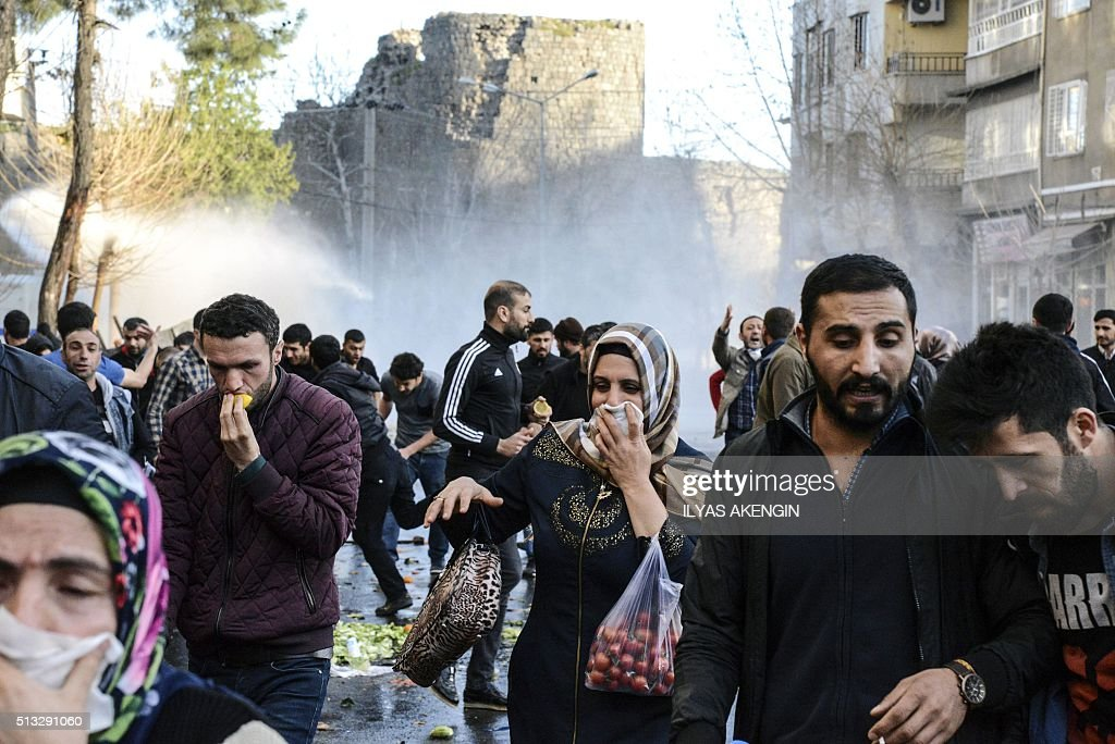 TOPSHOT People run away from tear gas during clashes between Turkish forces and Kurdish people in the centre of Diyarbakir protesting against a...