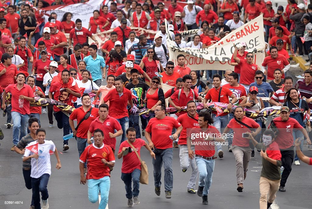 People run during a march to mark International Workers' Day, in San Salvador, on May 1, 2016. / AFP / Marvin RECINOS