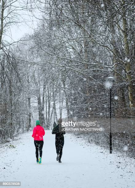 People run during snow fall on December 11 2017 in Sundbyberg near Stockholm High winds and heavy snow in Europe on Monday stranded thousands of...