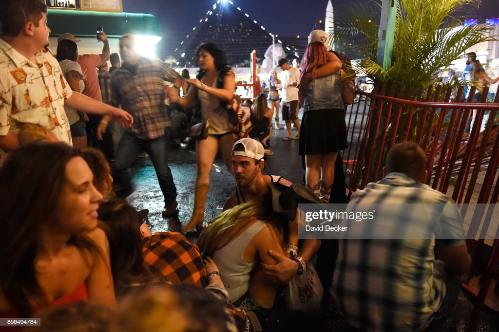 People run for cover at the Route 91 Harvest country music festival after apparent gun fire was heard on October 1, 2017 in Las Vegas, Nevada. There are reports of an active shooter around the Mandalay Bay Resort and Casino.