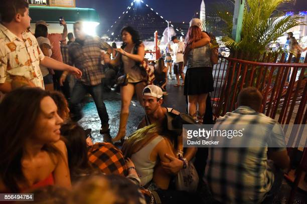 People run for cover at the Route 91 Harvest country music festival after apparent gun fire was heard on October 1 2017 in Las Vegas Nevada There are...