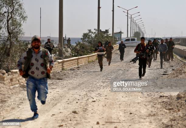 People run for cover following reported shelling by jihadists of the Islamic State group on March 29 2017 the Tabqa dam which has been recently...