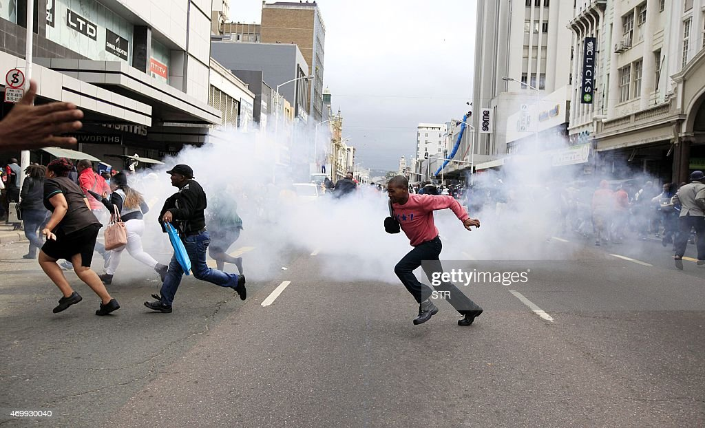 People run for cover from a stun grenade and tear gas after a skirmish between locals and foreign nationals as thousands of people take part in the...