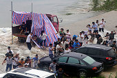 People run from a huge wave caused by the explosion of the dike between the Liangzi Lake and the Niushan Lake in on July 14 2016 in Wuhan Hubei...