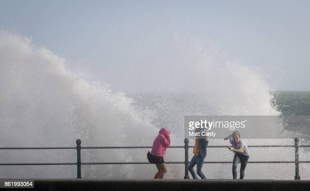 People run from a wave whipped up by Hurricane Ophelia as it crashes over the seafront in Penzance on October 16 2017 in Cornwall England Hurricane...