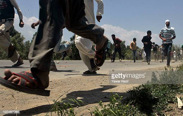 People run from police after being fired at during a protest of the deaths of three civilians in clashes over the weekend on June 28 2010 in Srinagar...