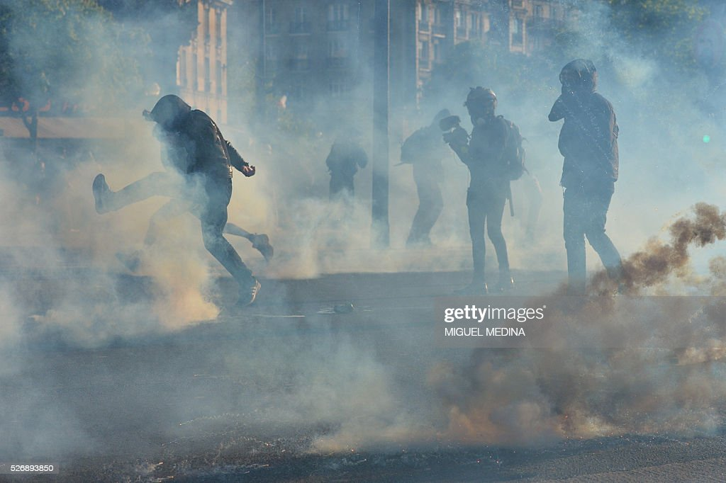 People run from smoke grenades during clashes between anti-riot police and protesters during the traditional May Day demonstration in Paris on May 1, 2016.