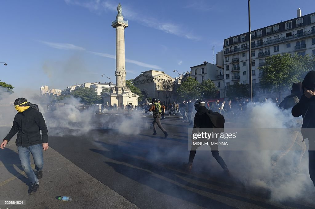 People run from tear gas during clashes between French anti riot police and protesters during the traditional May Day demonstration in Paris on May 1, 2016.