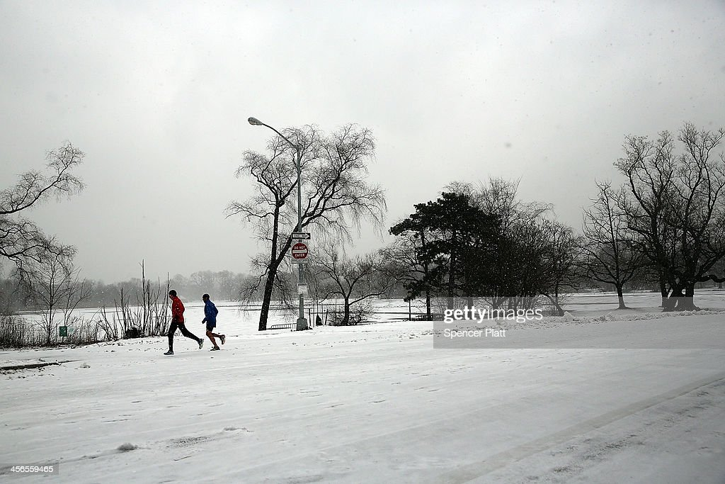 People run through Prospect Park during a snow storm on December 14, 2013 in the Brooklyn borough of New York City. Much of the Northeast was hit by a storm stretching over 1,000 miles that could result in at least a foot of snow on parts of New England.