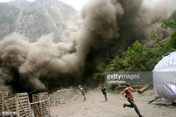 People run to escape from a landslide triggered by an aftershock on on May 17 2008 in Lixian County of Wenchuan Sichuan Province China A major...