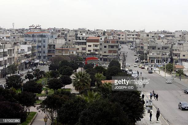 People run to hide following a rocket attack in the Akrama neighbourhood of the western city of Homs 162 kms north of Damascus on January 11 2012 A...