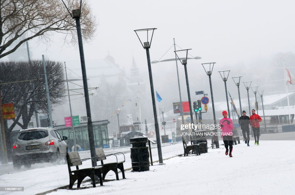 People run under the snow on Strandvagen in Stockholm on February 2, 2012. A cold snap kept Europe in its icy grip, pushing the death toll past 150 as countries from Italy to Ukraine struggled to cope with temperatures that reached record lows in some places. NACKSTRAND