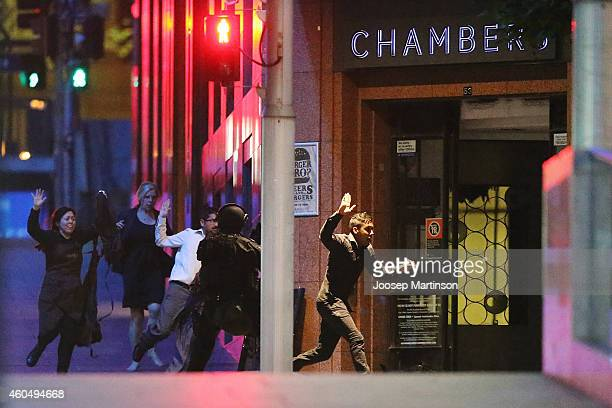 People run with their hands up from the Lindt Cafe Martin Place during a hostage standoff on December 16 2014 in Sydney Australia Police stormed the...