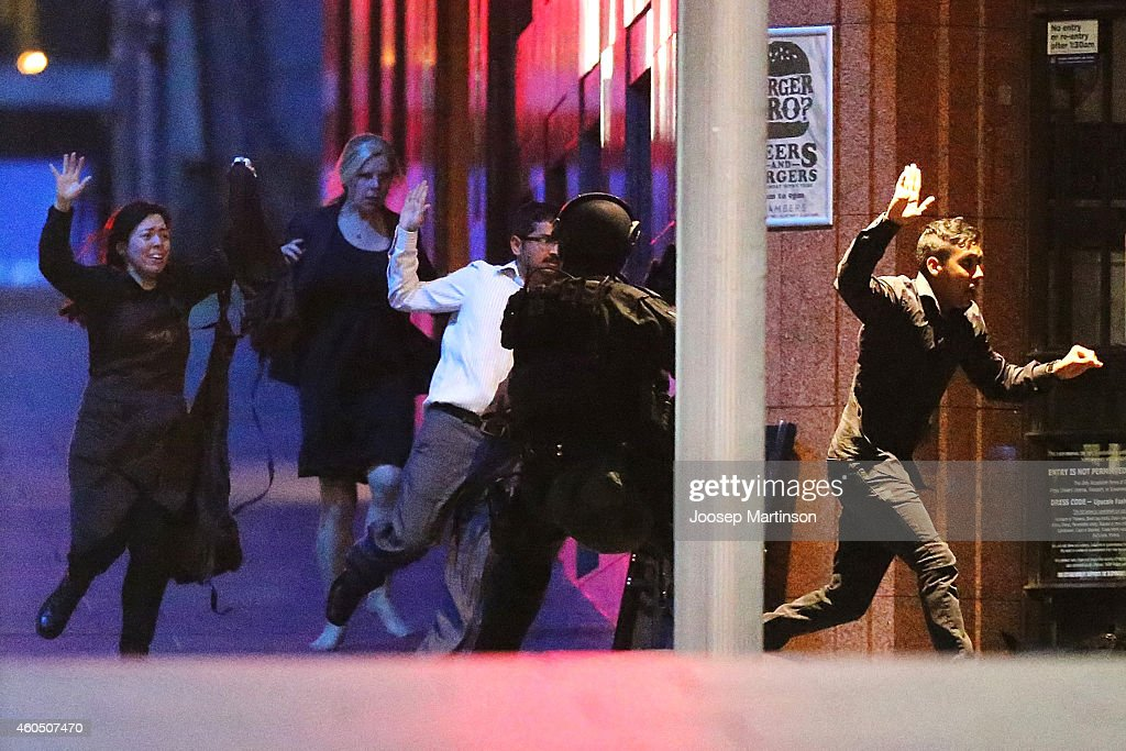People run with there hands up from the Lindt Cafe Martin Place during a hostage standoff on December 16 2014 in Sydney Australia Police stormed the...