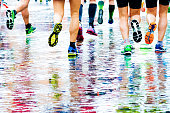 people running in a marathon on a wet surface