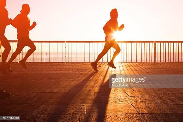 People running in Barcelona boardwalk on sunrise