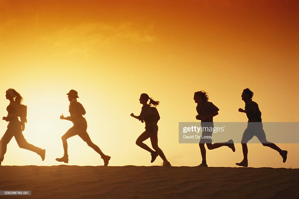 People running in desert at dusk, side view : Stock Photo