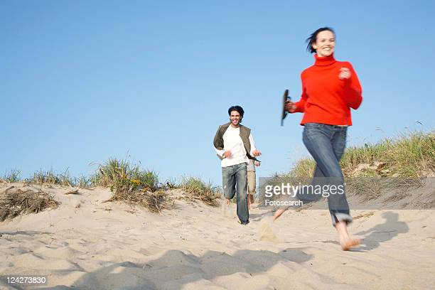 People running on beach (blurred motion, low angle view)
