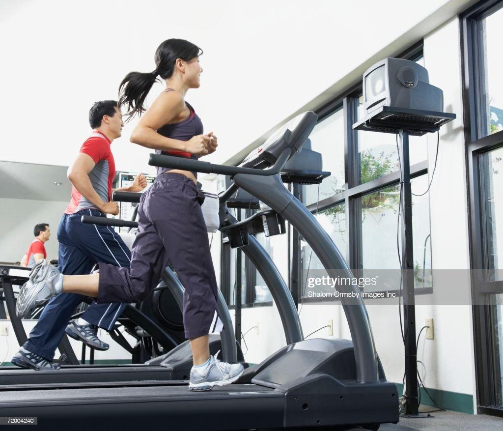 People running on treadmills in gym : Stock Photo