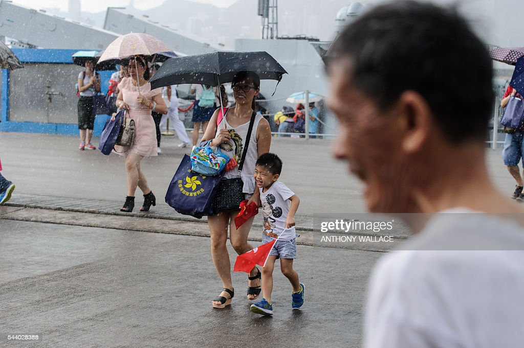People rush for shelter as it rains heavily during the open day of the Chinese People's Liberation Army (PLA) Navy Base at Stonecutter Island in Hong Kong on July 1, 2016, to mark the 19th anniversary of the Hong Kong handover to China . / AFP / Anthony Wallace