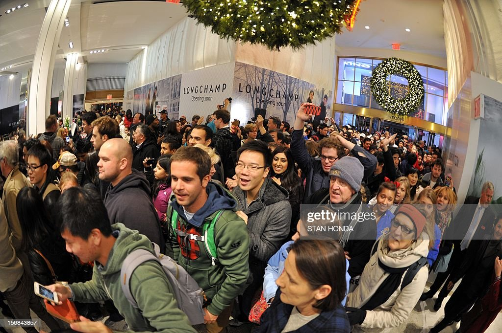 People rush into Macy's department store as they open at midnight (0500 GMT) on November 23, 2012 in New York to start the stores' 'Black Friday' shopping weekend. AFP PHOTO/Stan HONDA