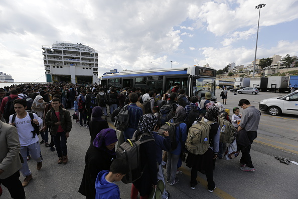 People rush into the busses that will bring them to the...