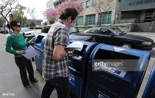 People rush to mail their tax returns before the last mail collection at a mailbox on the US Tax Day in Los Angeles on April 15 2010 Some post...