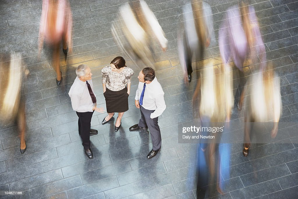 People rushing past business people talking