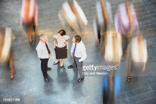 People rushing past business people talking : Stock Photo