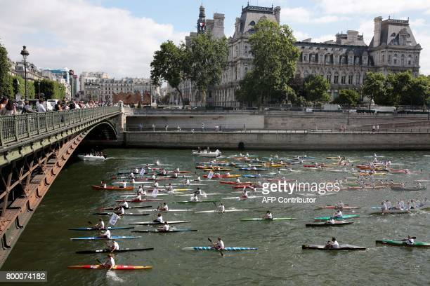 People sail on the Seine river in Paris on June 23 in a bid to promote the candidacy of the city of Paris for the Summer Olympics Games in 2024 / AFP...
