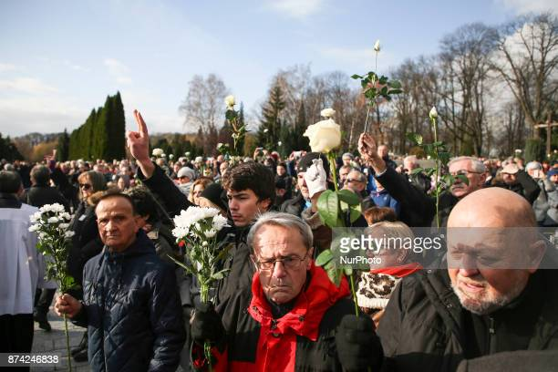 People salute withe white roses after Piotr Szczesny's funeral mass at Salwator cemetery in Krakow Poland on 14 November 2017 Piotr Szesny age 54 set...
