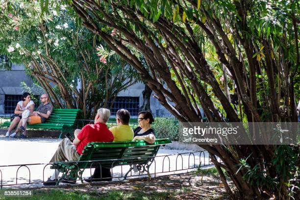 People sat on a bench in the sculpture garden at the National Museum Reina SofÕa Art Center