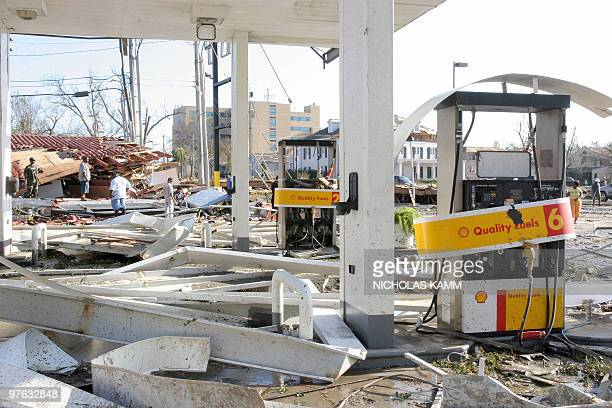People scavenge a destroyed gas station in Biloxi Mississppi 30 August 2005 after Hurricane Katrina hit the Gulf Coast Rescuers battled a...