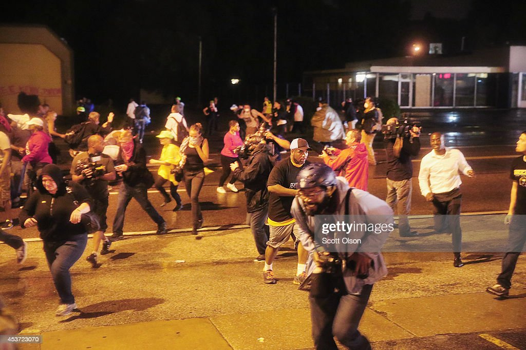 People scramble as police fire tear gas at demonstrators protesting the shooting of Michael Brown after they refused to honor the midnight curfew on August 17, 2014 in Ferguson, Missouri. The curfew was imposed on Saturday in an attempt to reign in the violence that has erupted nearly every night in the suburban St. Louis town since the shooting death of teenager Michael Brown by a Ferguson police officer on August 9.