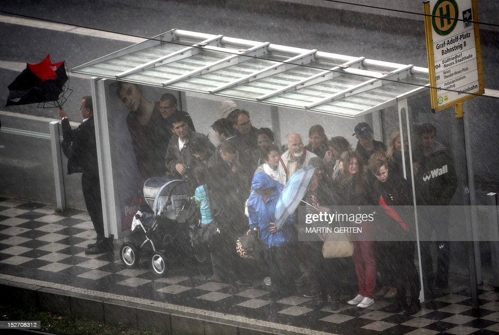 People search a shelter from the rain at a bus stop in Duesseldorf, western Germany, on September 24, 2012. Autumn brought rain and sinking temperatures to the region. AFP PHOTO / MARTIN GERTEN GERMANY OUT