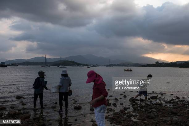 People search for clams along the shore in Hong Kong on October 7 2017 / AFP PHOTO / DALE DE LA REY