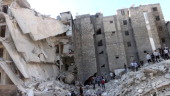 People search the rubble of a building which collapsed after it was allegedly bombed from the air during clashes between rebel fighter and...