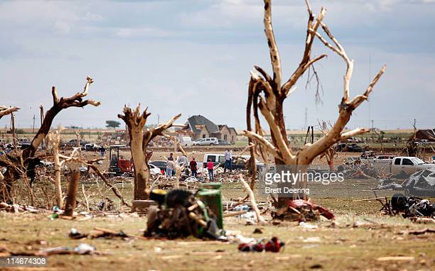 People search through the wreckage of the rural neighborhood struck by a tornado May 25 2011 in Piedmont Oklahoma The state medical examiner's office...
