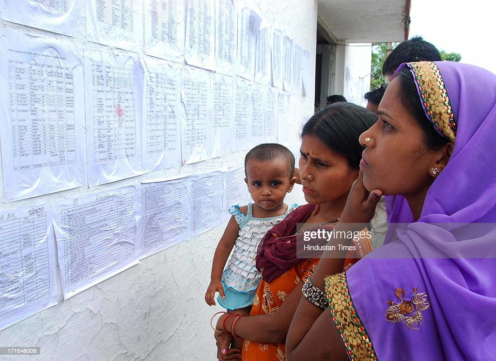 People searching for their relatives names in the list of the dead persons during disaster in Uttarakhand at Police Lines on June 26, 2013 in Dehradun, India. Some 1,000 people mostly the pilgrims to Badrinath and Kedarnath have died in flash floods and landslides caused by heavy downpours in India's Uttarakhand state.