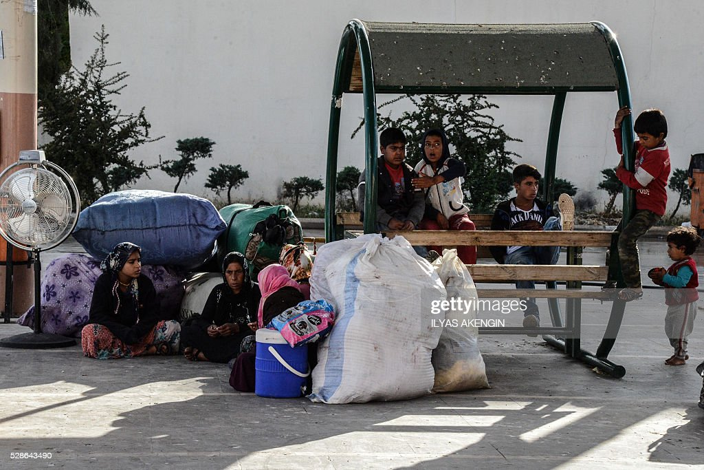 People seat with their belongings as they wait to leave kilis at a bus station on May 6, 2016 in Kilis. One person was killed and seven more wounded on May 5, 2016 when rockets fired from Syria slammed into the Turkish border region of Kilis, which has been regularly targeted by jihadists this year, the Dogan news agency said. / AFP / ILYAS