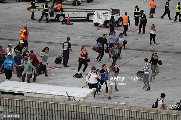 People seek cover on the tarmac of Fort LauderdaleHollywood International airport after a shooting took place near the baggage claim on January 6...