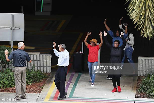 People seeking cover walk towards police with their arms raised outside the Fort LauderdaleHollywood International airport after a shooting took...