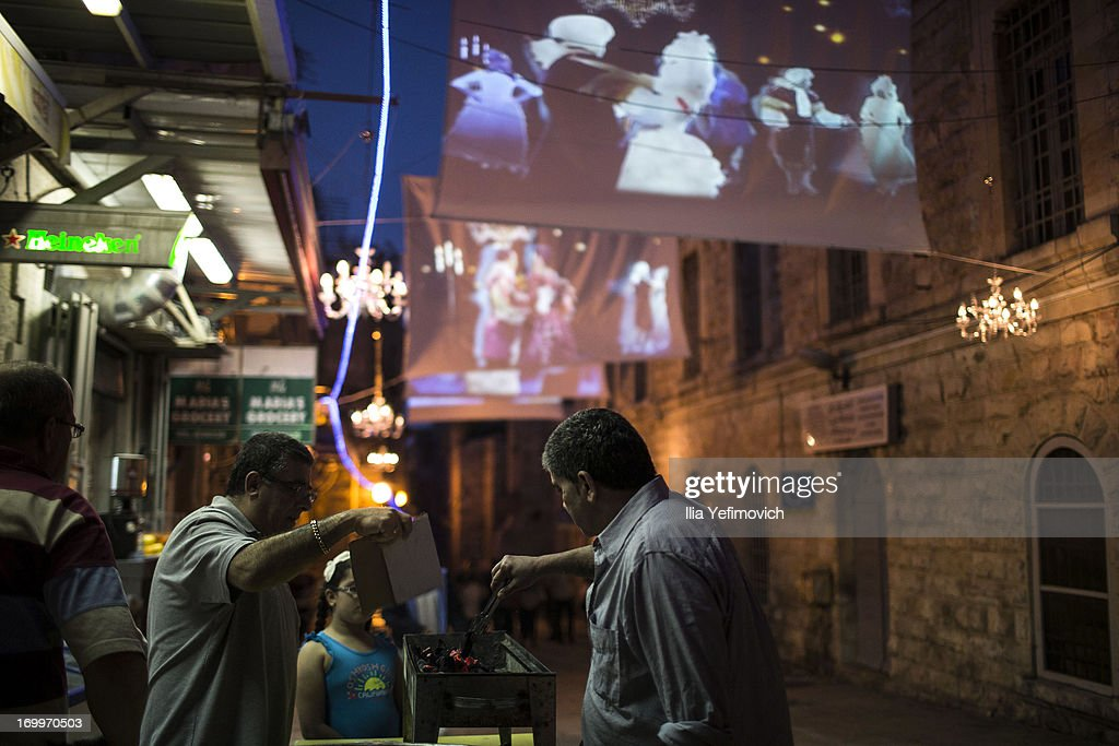 People sell food under a light installation during the annual Jerusalem Festival of Light on June 5, 2013 in Jerusalem, Israel. During the festival light installations are projected onto the historic buildings of Jerusalem's Old City.