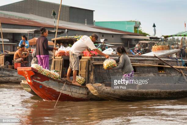 People selling tomatoes from a boat in the floating market Cai Rang near Can Tho Mekong River Delta Vietnam