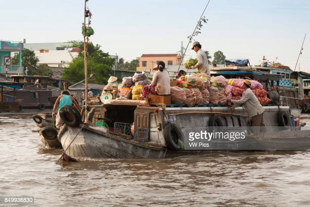 People selling vegetables from a boat in the floating market Cai Rang near Can Tho Mekong River Delta Vietnam