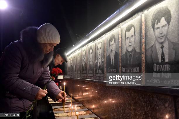 TOPSHOT People set candles and lay flowers at the monument to Chernobyl victims in Slavutich the city of the power station's personnel live some 50...