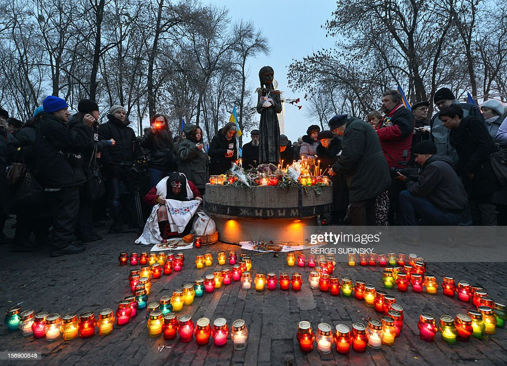 People set candles at the memorial dedicated to the victims of the Holodomor famine during a ceremony in Kiev on November 24, 2012. Ukraine marked 80 years since the Stalin-era Holodomor famine, one of the darkest pages in its entire history that left millions dead and which is regarded by many as a genocide. The 1932-33 famine took place as harvests dwindled and Josef Stalin's Soviet police enforced the brutal policy of collectivising agriculture by requisitioning grain and other foodstuffs. AFP PHOTO/ SERGEI SUPINSKY