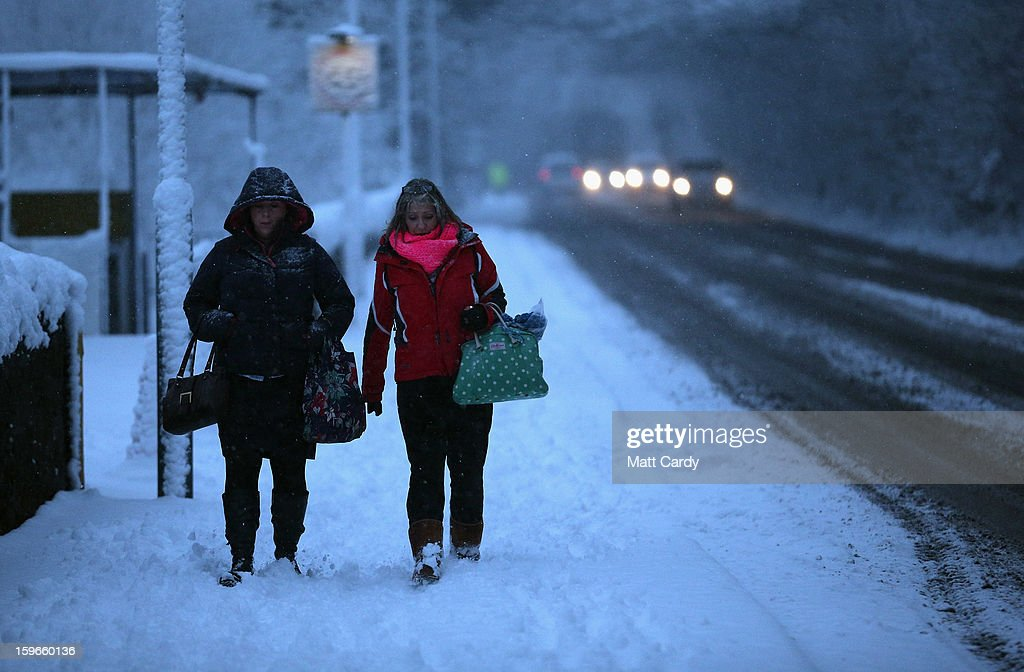 People set out in the early morning light in Radstock on January 18, 2013 near Bath, England. Heavy snow is bringing widespread disruption to many parts of the UK.