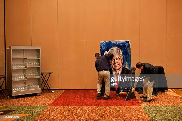 People set up a painting of Newt Gingrich by artist Steve Penley to a rally March 6 2012 in Atlanta Georgia Republican presidential candidate...