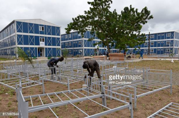 People set up beds in the dormitory at the National Institute of Youth and Sports on July 17 2017 in the Marcory neighbourhood in Abidjan ahead of...